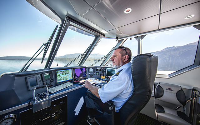 Real Journeys' worker at the helm of one of the company's vessels.
