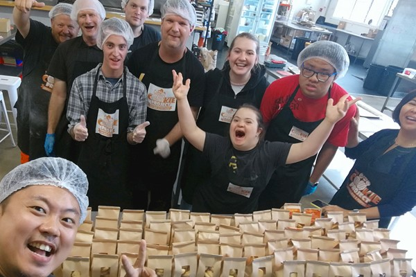 Photo of staff at The Cookie Project with bags of biscuits