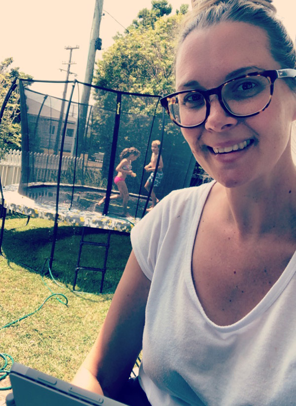 Diversity Manager Claire Stuart works from home while her children Zoe and Micah cool off on the trampoline