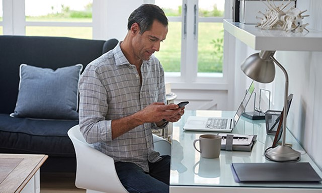 Man working on phone and laptop at home