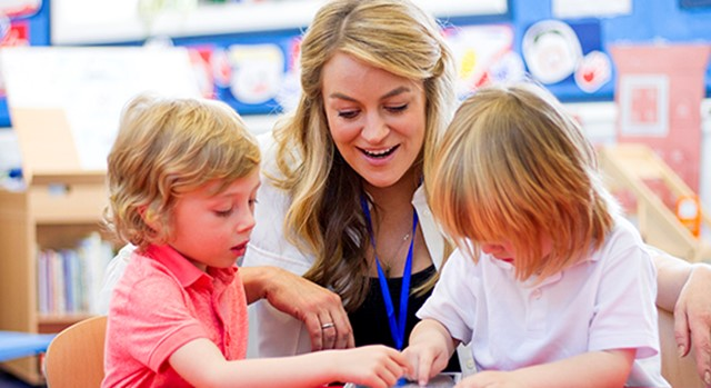 Teacher aide helping two small children in a classroom