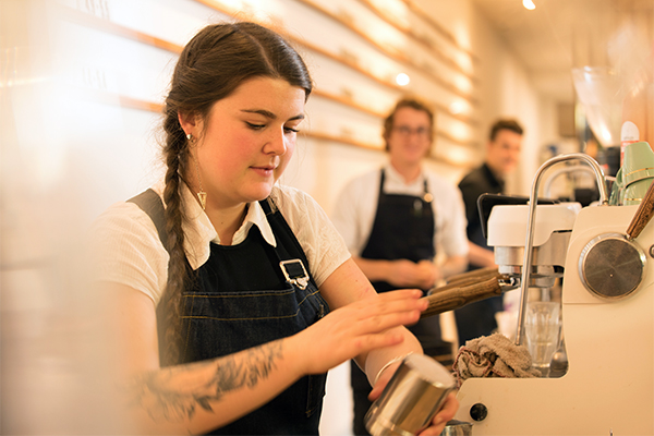 photo of female barista making coffee