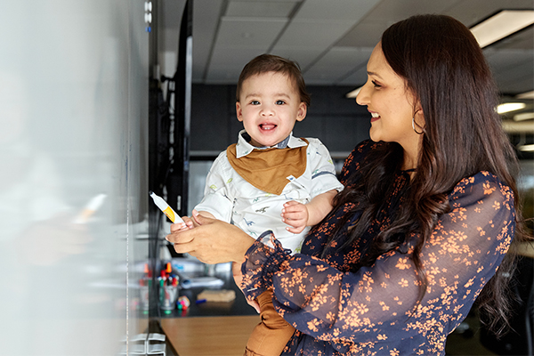 Photo of mother working at whiteboard holding child