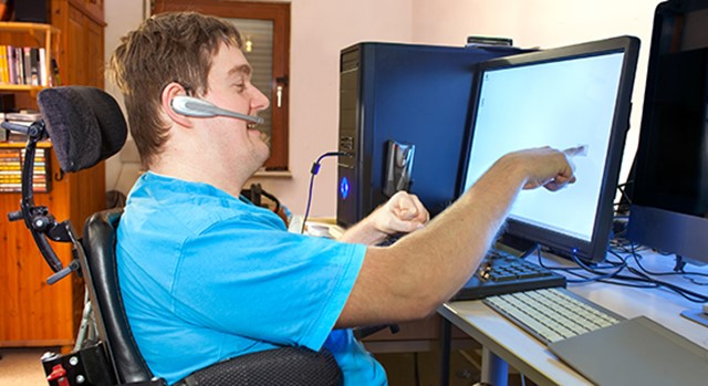 Young disabled man using touch screen to work