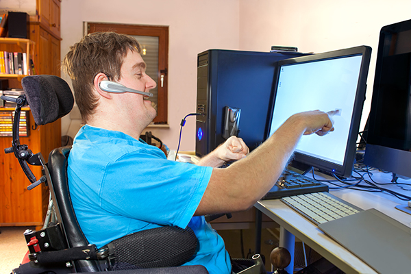 Young disabled man uses touch screen for work